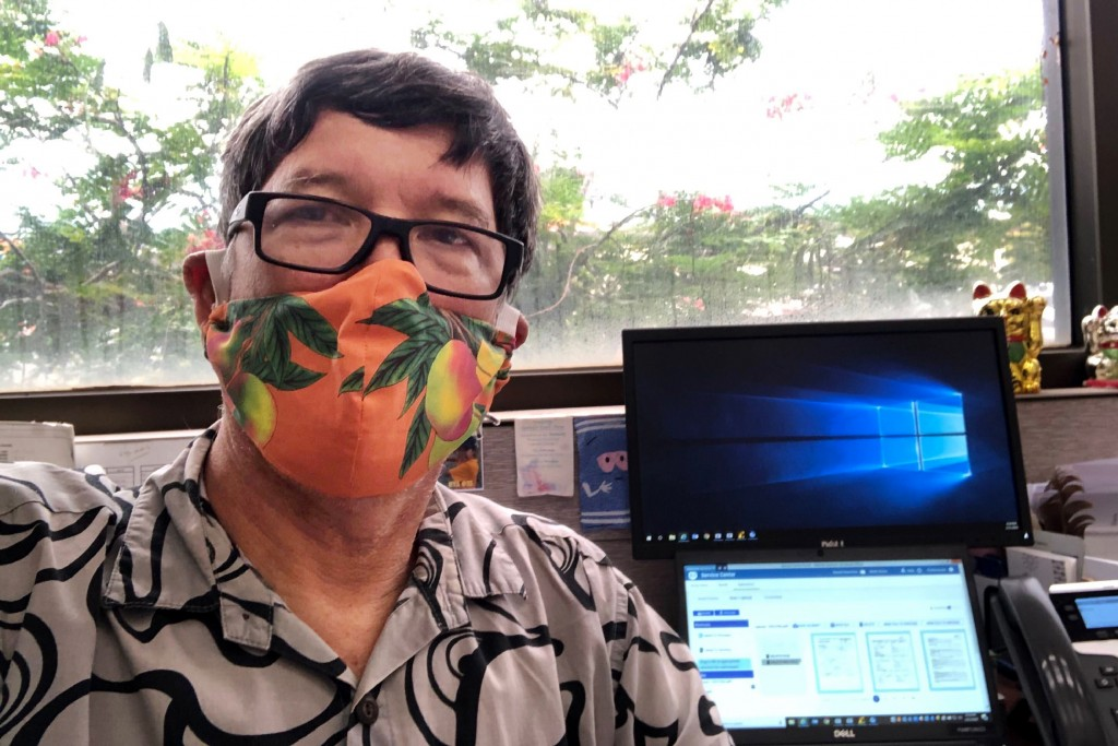 This April 3, 2020 photo provided by Candy Suiso shows her husband at work in Waipahu, Hawaii, wearing a mango print cloth mask made by her sister. Fa...