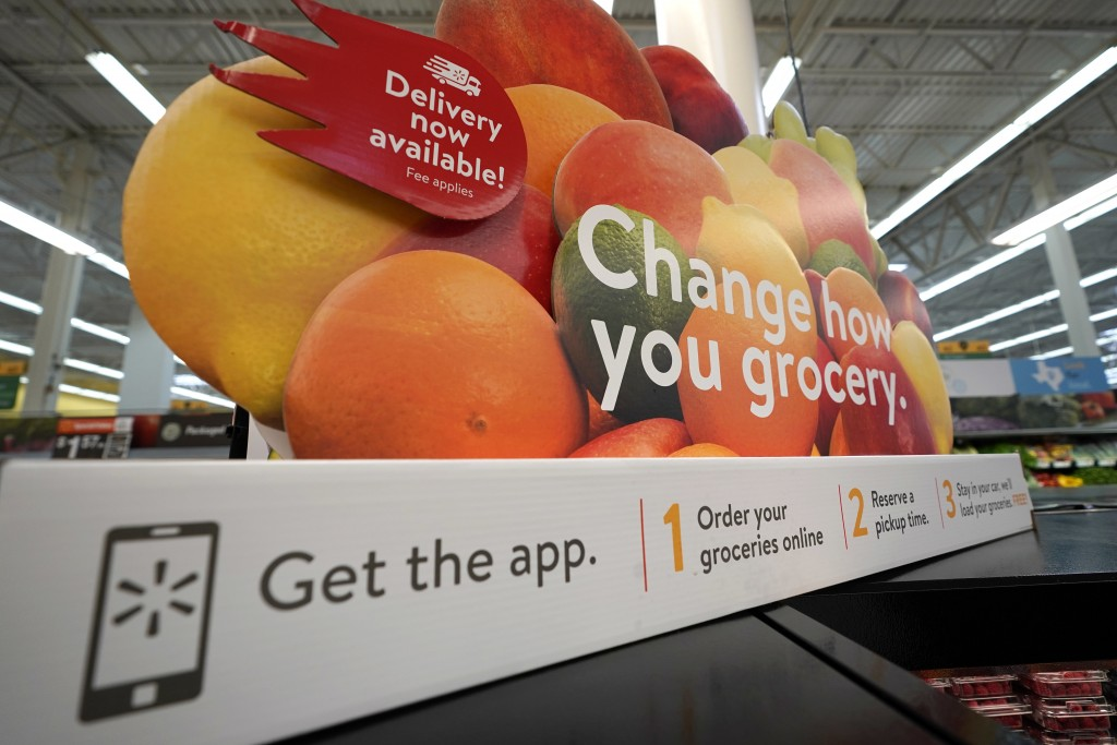 FILE - In this Nov. 9, 2018, file photo a sign promotes online and home delivery of groceries at a Walmart Supercenter in Houston. A leap in U.S. unem...