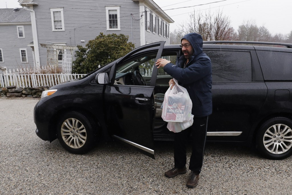 FILE - In this Friday, April 3, 2020, file photo, Instacart worker Arthur Berte delivers groceries to a home in East Derry, N.H. Some app-based delive...