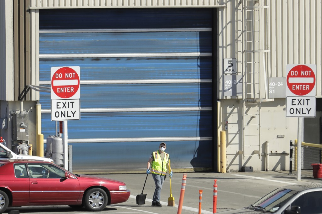 FILE - In this April 13, 2020 file photo, a worker wears a mask as he cleans up an area outside an entrance at Boeing Co.'s airplane assembly facility...