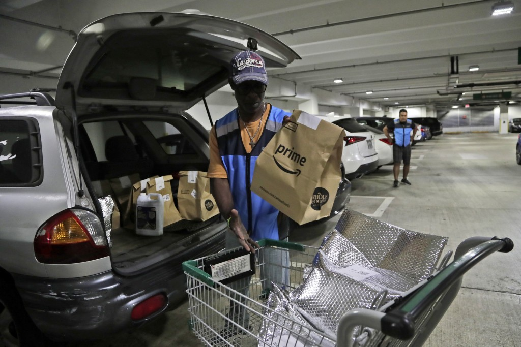 FILE - In this March 31, 2020, file photo, Samuel Diaz, a delivery worker for Amazon Prime, loads his vehicle with groceries from Whole Foods, in Miam...