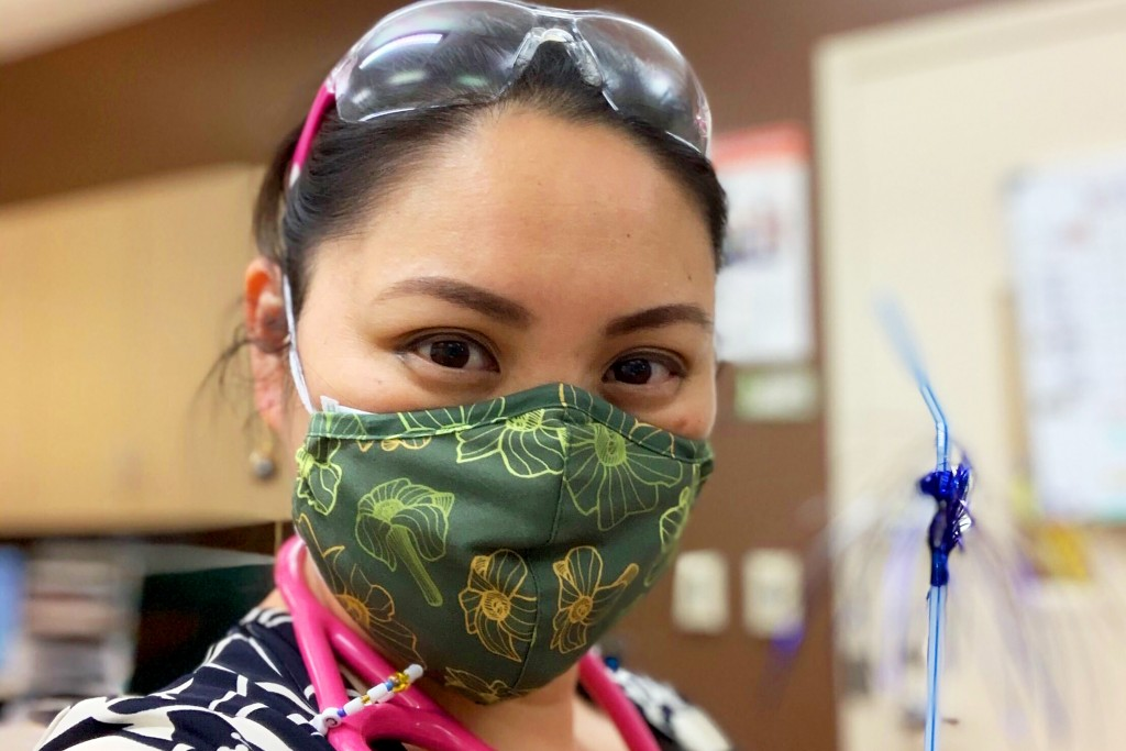 This April 3, 2020 selfie photo provided by Coty George shows George in Waianae, Hawaii, wearing a green cloth mask with yellow and orange puakenikeni...