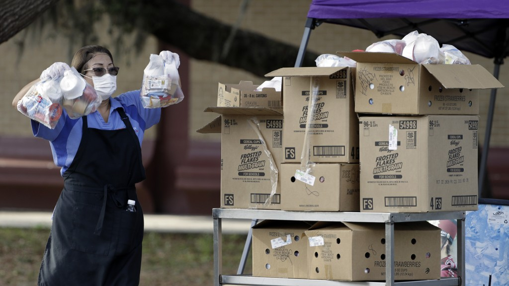 A Hillsborough County lunch room worker holds up food while parents wait in a line Wednesday, April 15, 2020, at the Brandon High School in Brandon, F...