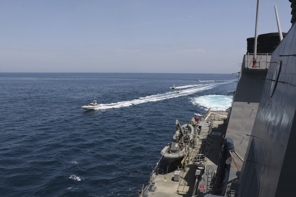 In this Wednesday, April 15, 2020, photo made available by U.S. Navy, Iranian Revolutionary Guard vessels sail close to U.S. military ships in the Per...