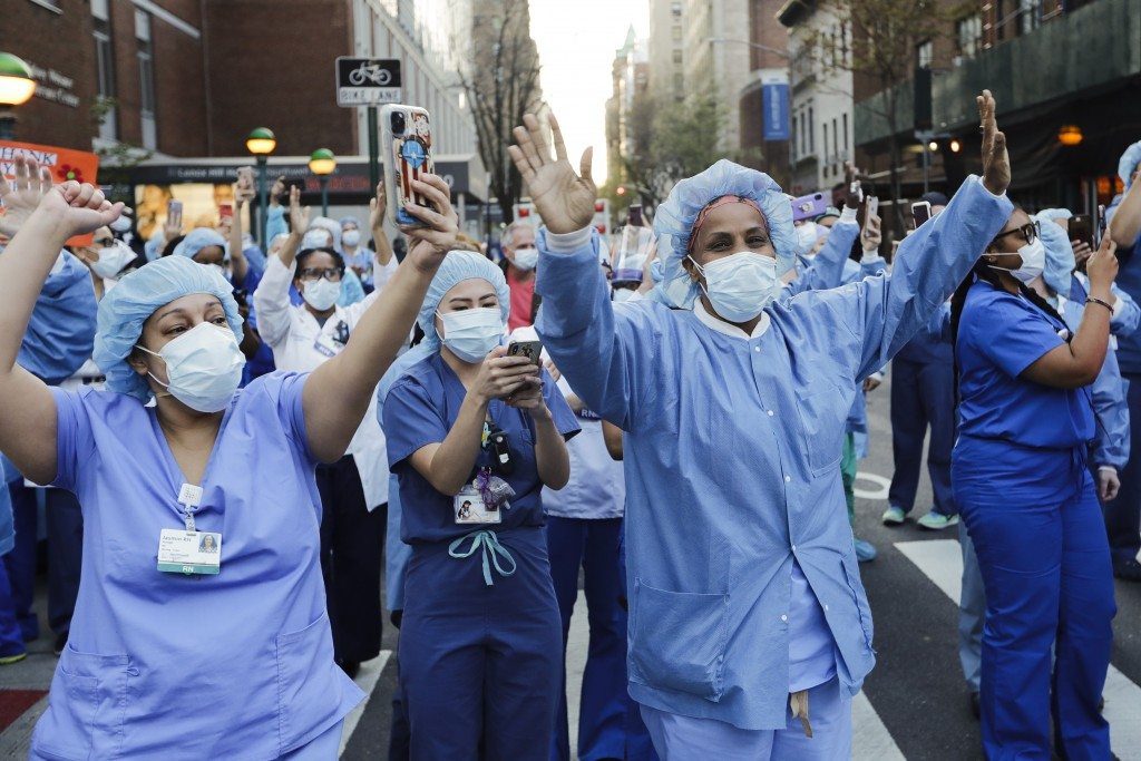 Nurses and medical workers react as police officers and pedestrians cheer them outside Lenox Hill Hospital Wednesday, April 15, 2020, in New York. (AP...