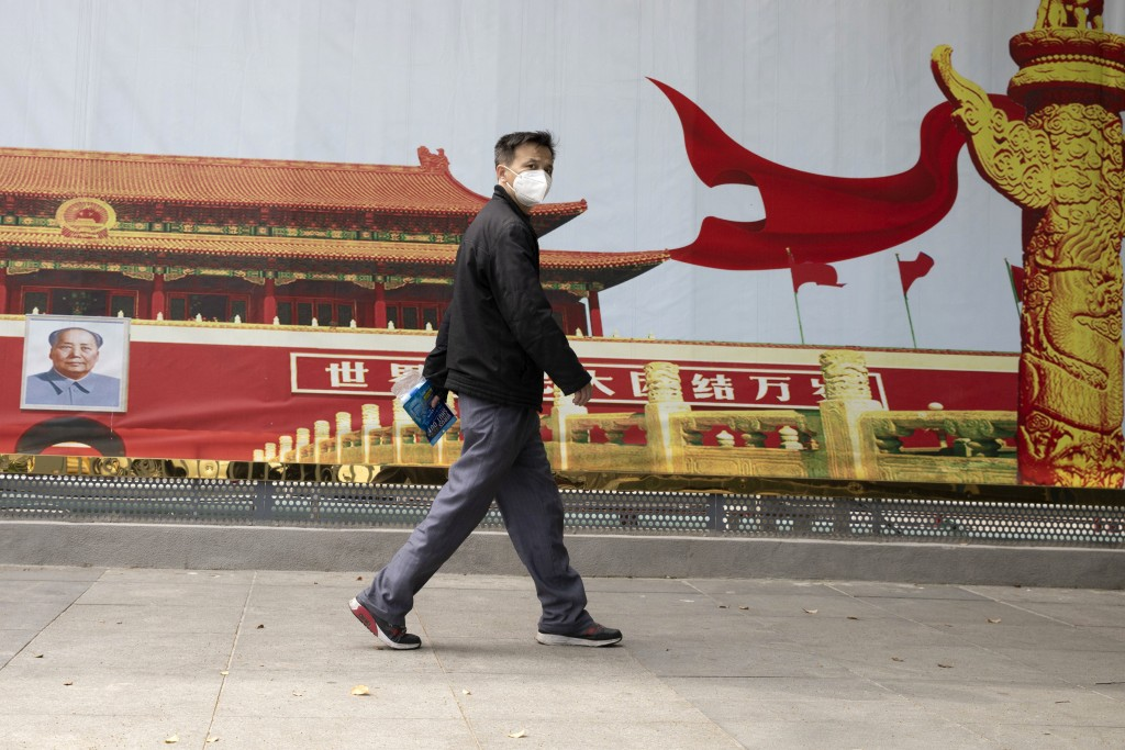 A resident wearing a mask against coronavirus walks past government propaganda poster featuring Tiananmen Gate in Wuhan in central China's Hubei provi...