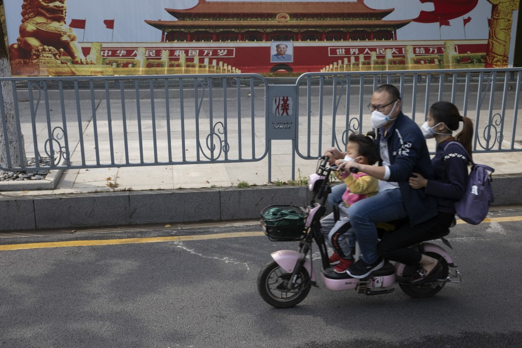 Residents wearing masks against the new coronavirus pass by government propaganda posters featuring Tiananmen Gate in Wuhan in central China's Hubei p...