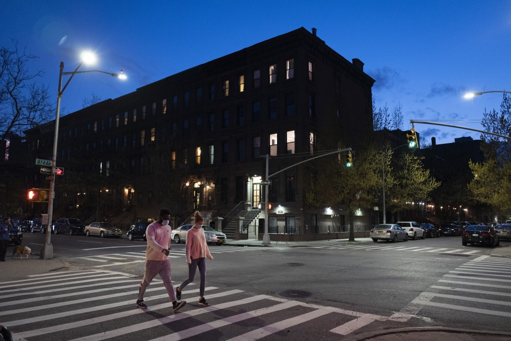 People wearing masks cross the street at Langston Hughes Place in Harlem, Wednesday night, April 15, 2020 during the coronavirus pandemic in New York....