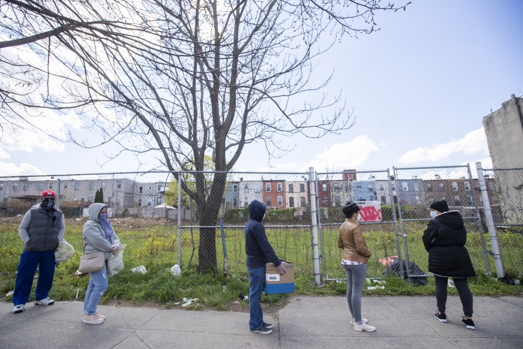 People wait in line at The Campaign Against Hunger food pantry, Thursday, April 16, 2020, in the Bedford-Stuyvesant neighborhood of the Brooklyn borou...