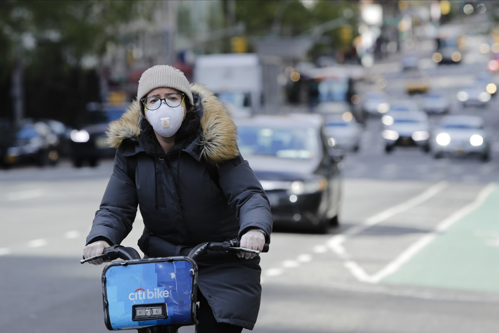 A woman wearing a mask rides a bicycle along second avenue Thursday, April 16, 2020, in New York. (AP Photo/Frank Franklin II)