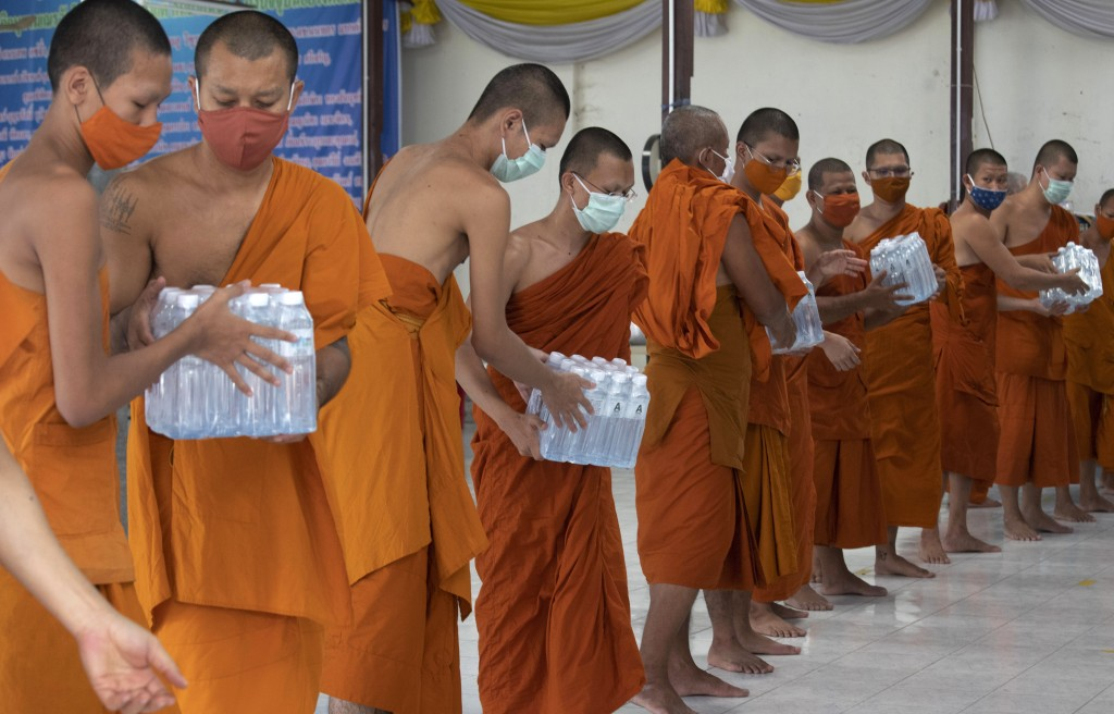 Thai Buddhist monks wearing face masks to protect themselves from the coronavirus pass pack of water after their devotees donated it to Molilokayaram ...