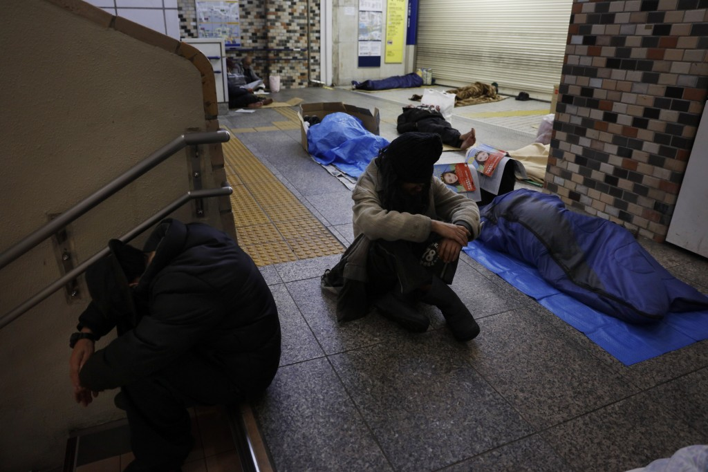 FILE - In this Jan. 9, 2020, file photo, homeless people sleep on the concrete floor of Shinjuku Station, in Tokyo. A group representing the homeless ...
