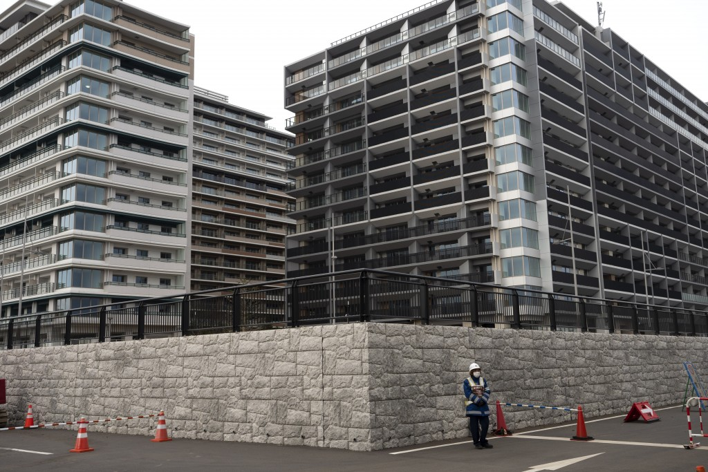 FILE  - In this March 23, 2020, file photo, a guard stands in front of apartment buildings at the athletes' village for the Tokyo 2020 Olympics in Tok...