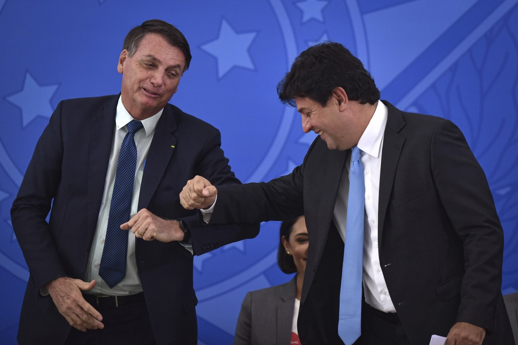 Brazil's President Jair Bolsonaro, left, greets his outgoing Health Minister Luiz Henrique Mandetta during the swearing-in ceremony for the new Health...