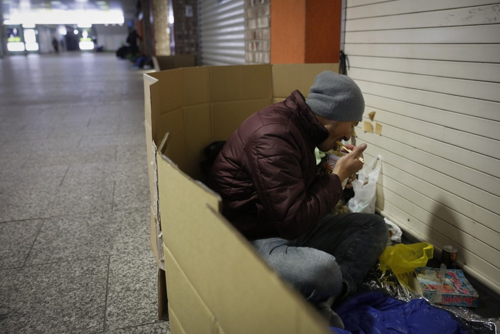 FILE - In this Jan. 7, 2020, file photo, a homeless man eats his late dinner in a cardboard box at Shinjuku Station, in Tokyo. A group representing th...