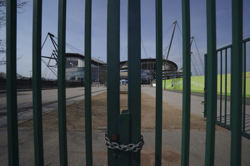 FILE - In this April 9, 2020, file photo, Gates stand locked outside the closed Manchester City Etihad Stadium, in Manchester, northern England, as th...