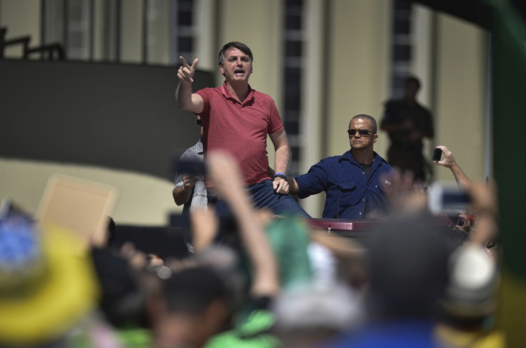 Brazil's President Jair Bolsonaro speaks to supporters during a protest in front the army's headquarters during the Army day, amid the new coronavirus...