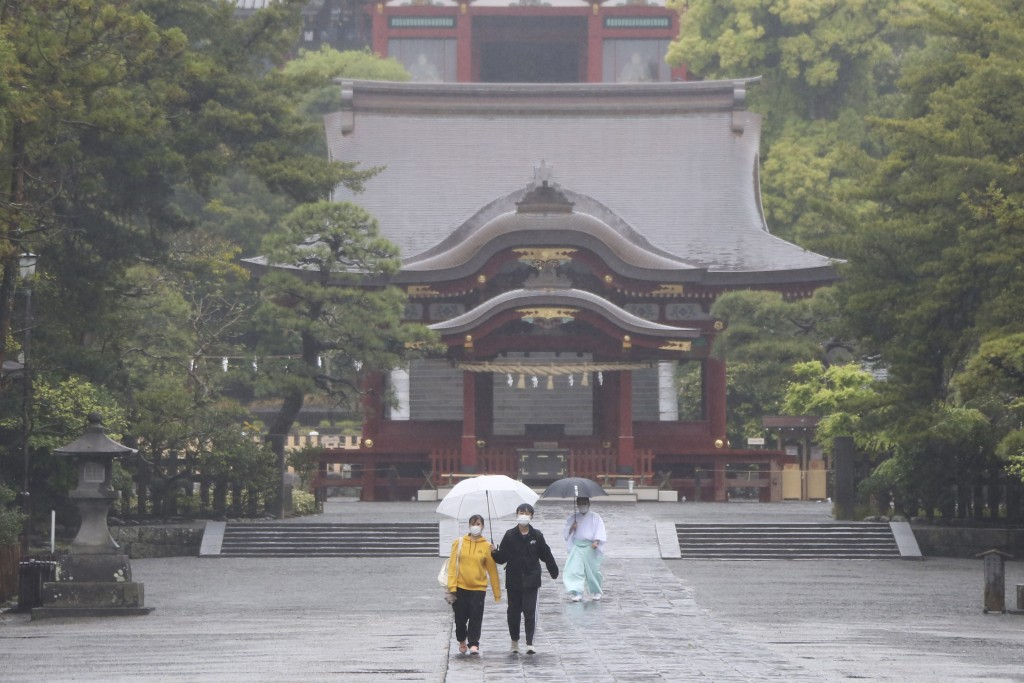A few people wearing face masks to protect against the spread of the new coronavirus walk in the rain in quiet Tsurugaoka Hachimangu Shinto shrine in ...