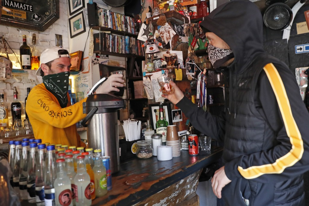 Derek Tigue, left, toasts a walk-in customer at FMN General Store, formerly the Forgtmenot bar, during the coronavirus outbreak, Wednesday, April 15, ...