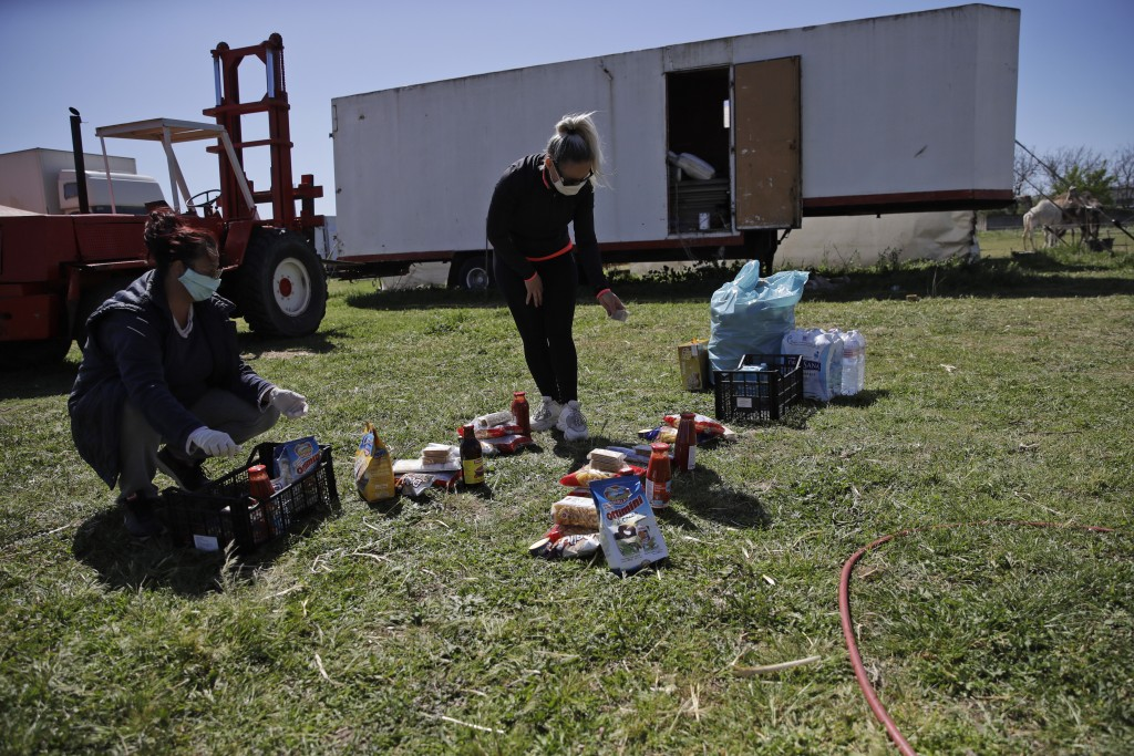 Verusca Coda Prin, left, and Anamaria Bud collect goods just donated by Civil protection, at the Romina Orfei Circus, parked in San Nicola la Strada, ...