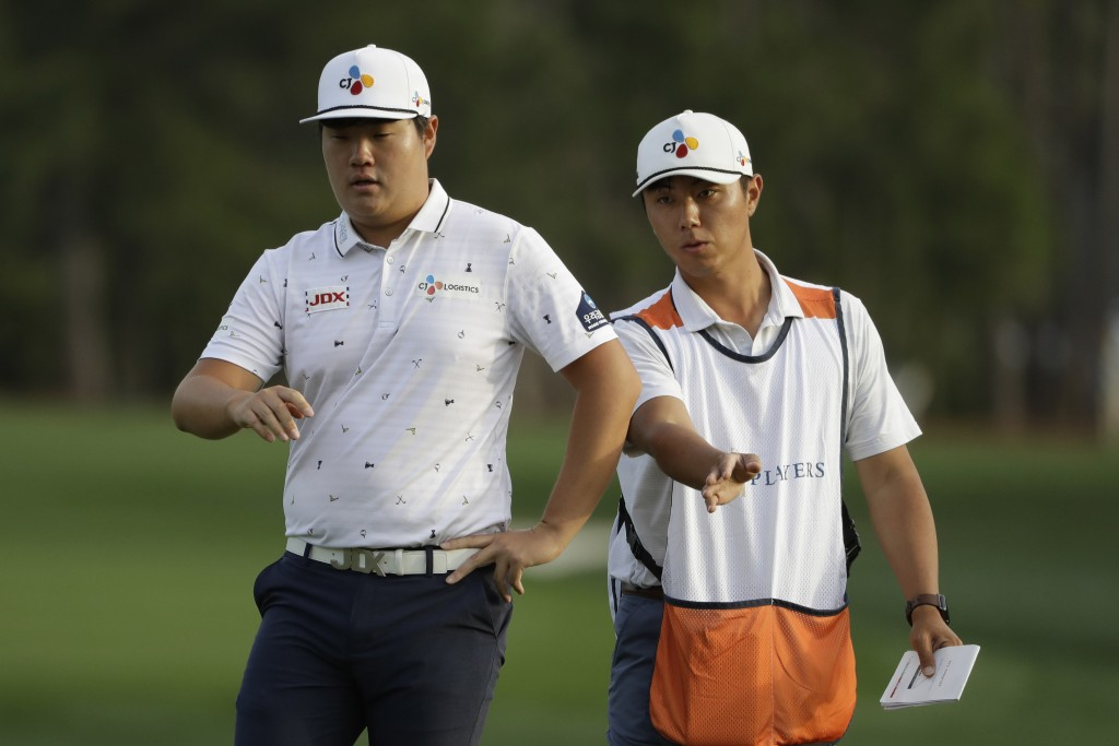 FILE - In this March 12, 2020, file photo, Sungjae Im, of South Korea, left, and his caddie Ki Tank Lee gesture on the 11th tee during the first round...