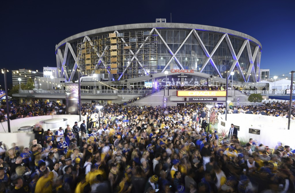 FILE - In this June 8, 2018,  long exposure file photo, Golden State Warriors fans celebrate outside Oracle Arena in Oakland, Calif. With the distinct...