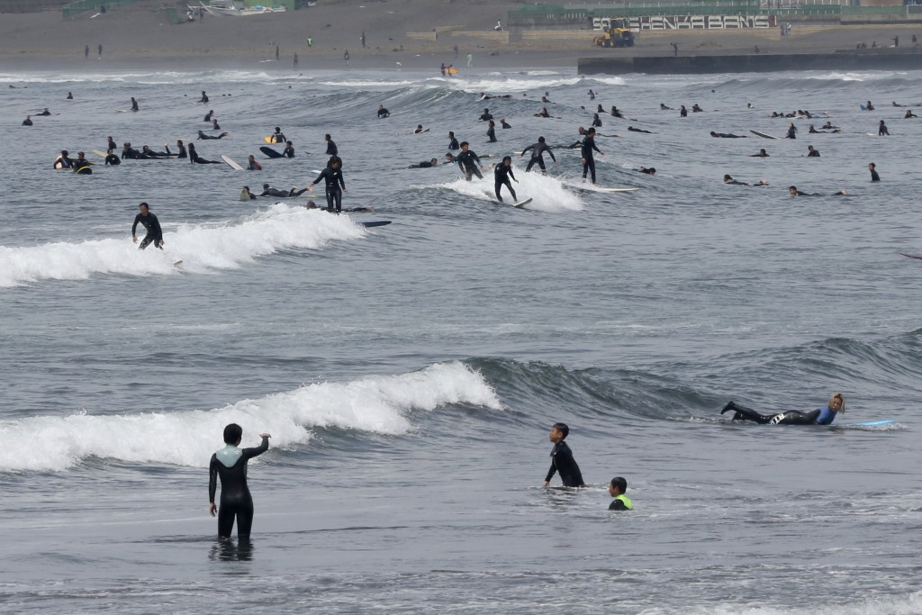 People go surfing off Katase Kaigan beach in Fujisawa, near Tokyo, Tuesday, April 21, 2020.  Japan's Prime Minister Shinzo Abe expanded a state of eme...
