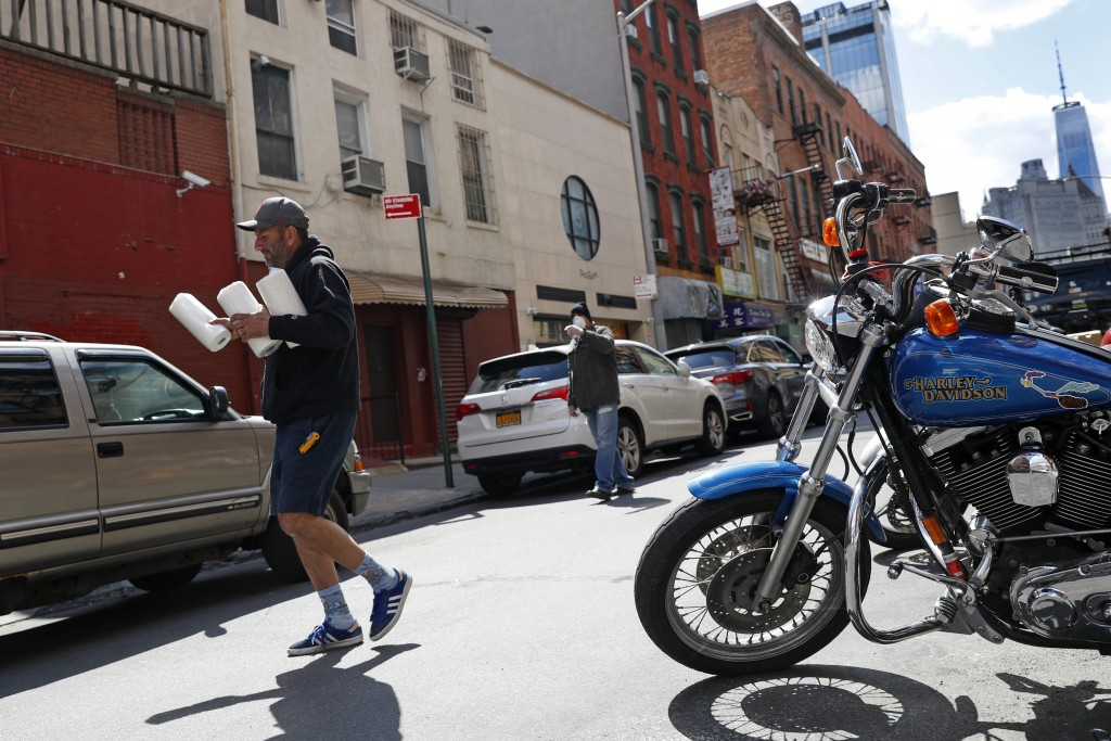 FMN General Store owner Paul Sierros carries paper towels to a customer's car during the coronavirus outbreak, Wednesday, April 15, 2020, in New York....