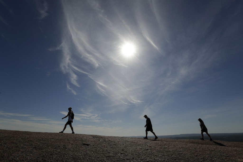 Following social distancing rules and wearing face coverings, visitors hike through Enchanted Rock State Park, Monday, April 20, 2020, in Fredericksbu...