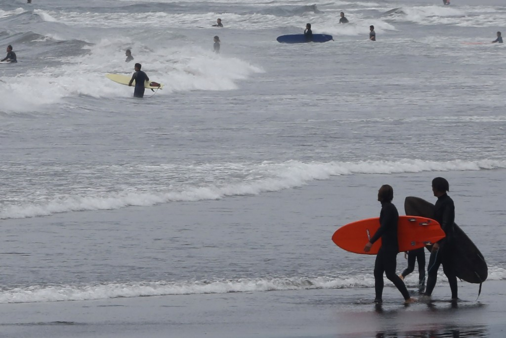 A couple of surfers walks on Katase Kaigan beach in Fujisawa, near Tokyo, Tuesday, April 21, 2020.  Japan's Prime Minister Shinzo Abe expanded a state...
