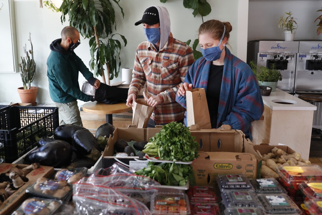 Justin Whitkin, center, and Elizabeth Boileau, right, shop for produce at Clementine Bakery in the Brooklyn borough of New York, during the coronaviru...