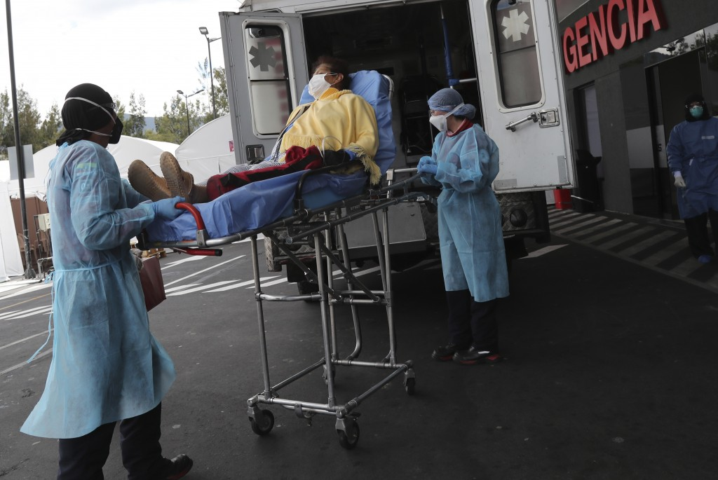 A woman suspected of suffering from COVID-19 disease arrives by ambulance to the Hospital del Seguro Social Quito Sur in Quito, Ecuador, Monday, April...