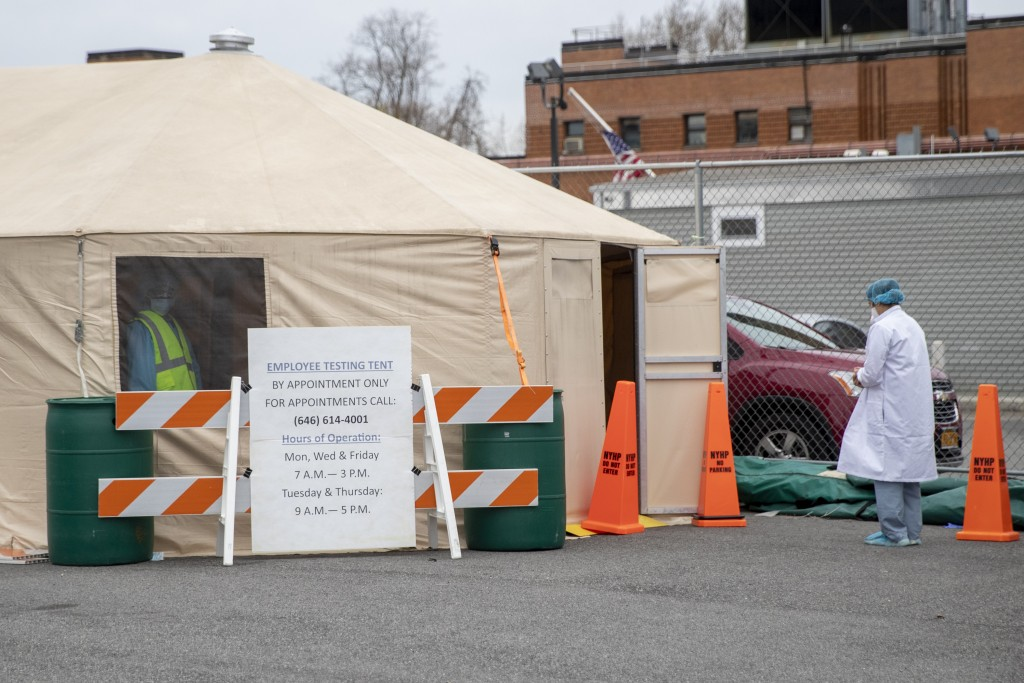 A medic waits outside a tent for her turn to be tested for COVID-19 at Queens Hospital Center, Monday, April 20, 2020, in the Jamaica neighborhood of ...