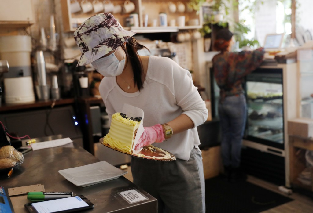 Assistant Manager Tiffany Wong moves a cake onto a smaller plate at Clementine Bakery in the Brooklyn borough of New York, during the coronavirus outb...
