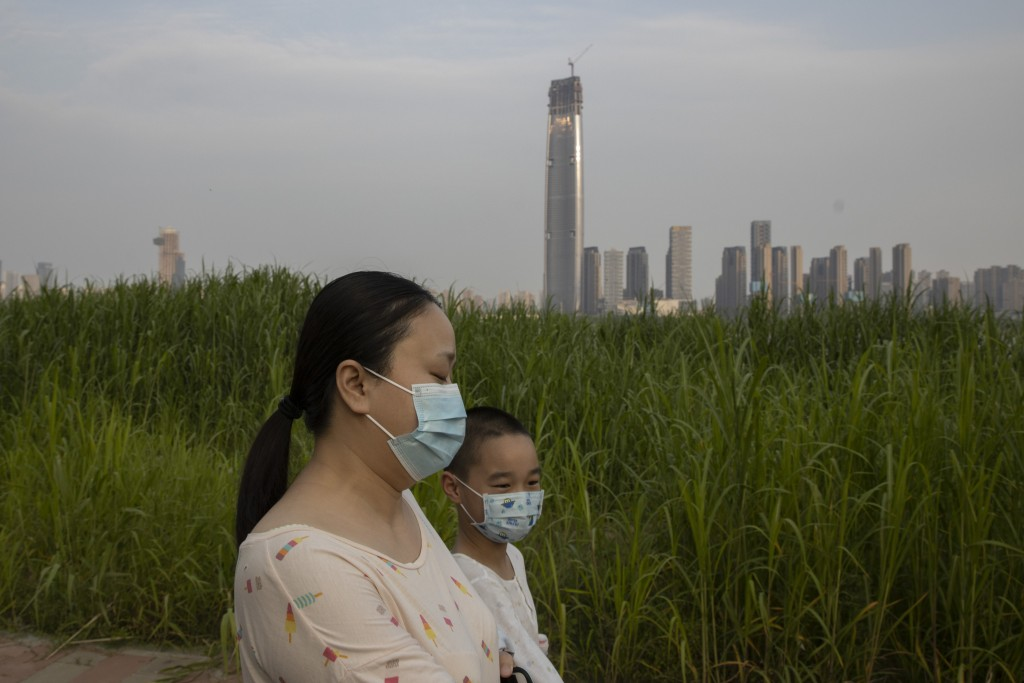 In this April 16, 2020, photo, residents wearing masks against the coronavirus walk past reeds and the cityscape along the Yangtze River in Wuhan in c...