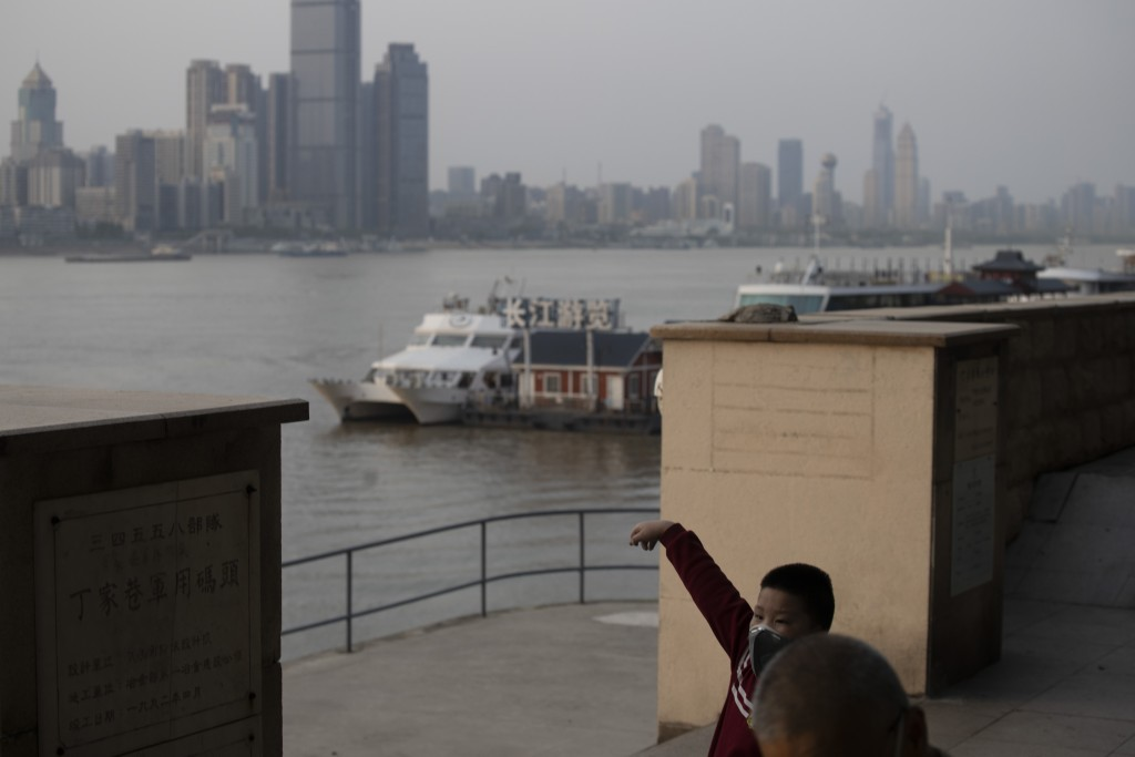 In this April 8, 2020, photo, a child wearing a mask against the coronavirus stretches near a ferry terminal along the Yangtze River in Wuhan in centr...