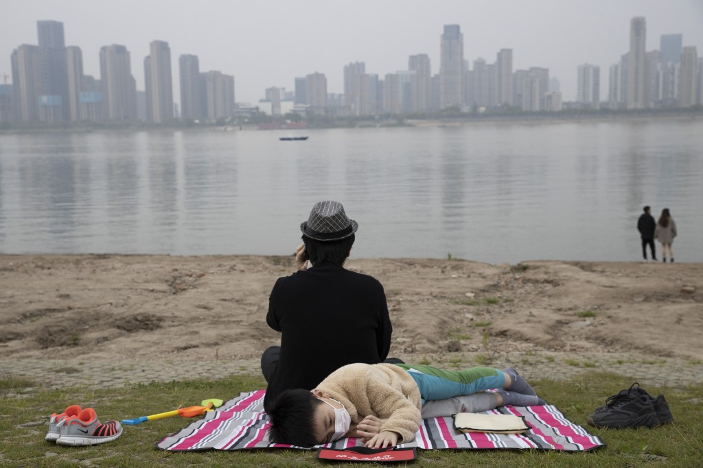 In this April 16, 2020, photo, a child wearing a mask against the coronavirus rest on the banks of the Yangtze River in Wuhan in central China's Hubei...