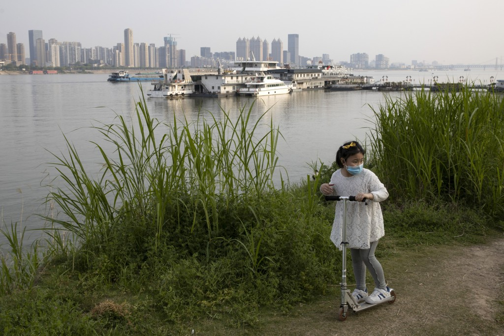 In this April 16, 2020, photo, a child wearing a mask against coronavirus rides her push bike along the banks of the Yangtze River in Wuhan in central...