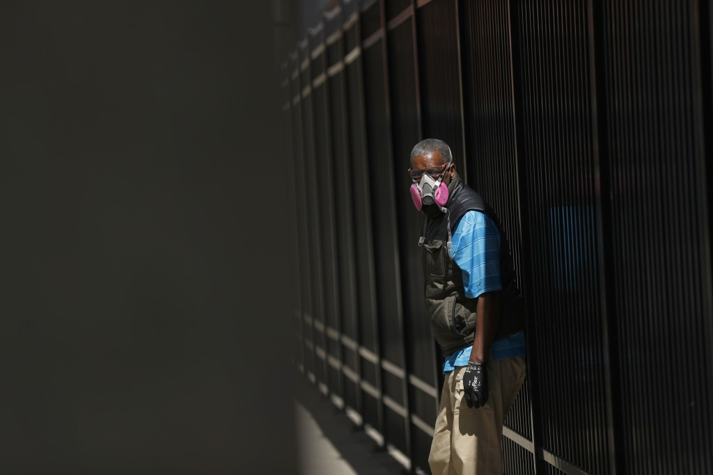 A man wears a protective mask while waiting for a bus in Detroit, Wednesday, April 8, 2020. As of mid April 2020, it's not yet clear how often people ...