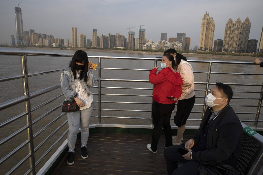 In this April 8, 2020, photo, passengers cross the Yangtze River on a ferry in Wuhan in central China's Hubei province. The reopening of ferry service...