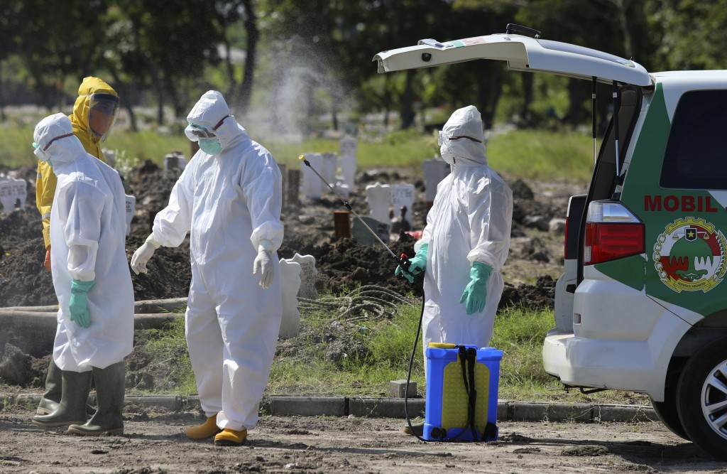A health worker sprays a colleague with disinfectant after the burial of the body of a coronavirus victim at a cemetery in Surabaya, East Java, Indone...