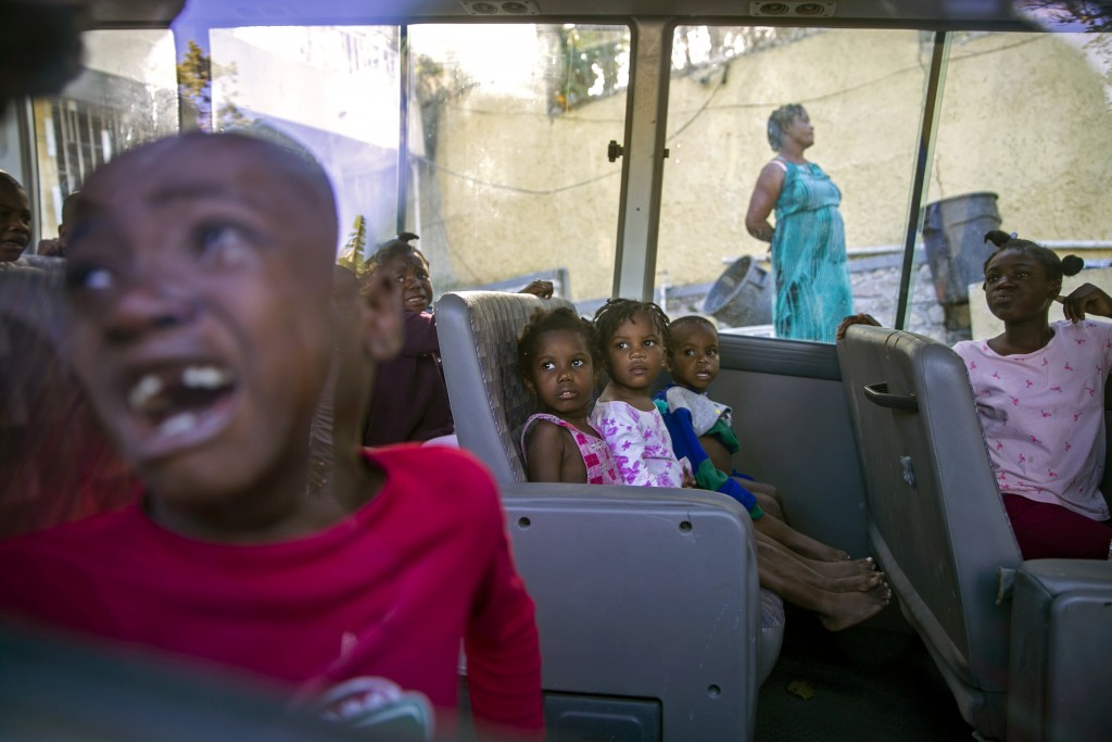 FILE - In this Feb. 14, 2020 file photo, orphans sit inside a social services bus after police removed them from a children's home run by the Orphanag...