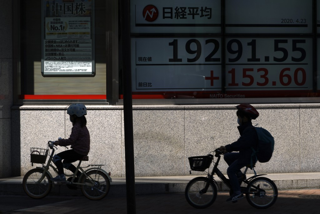 Children wearing masks against the spread of the new coronavirus ride bicycle past an electronic stock board showing Japan's Nikkei 225 index at a sec...