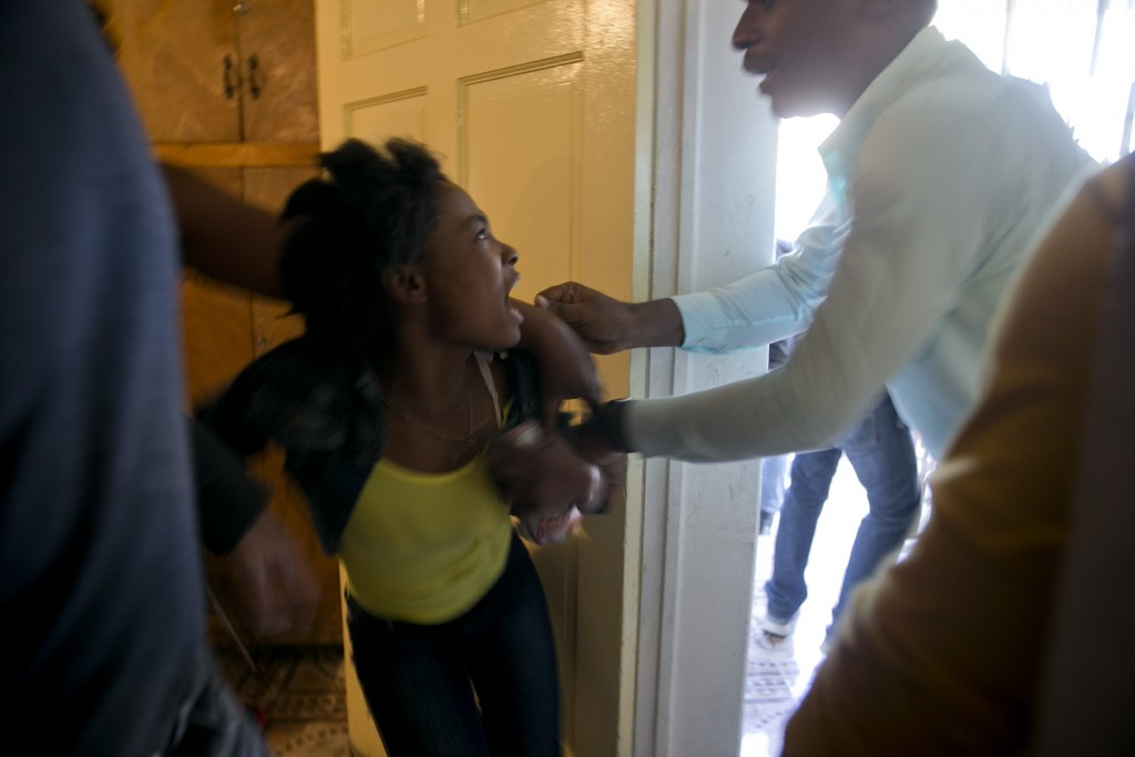 """FILE - In this Feb. 14, 2020 file photo, a girl yells, """"I don't want to go!"""" as a state employee attempts to remove her from one of the children's hom..."""