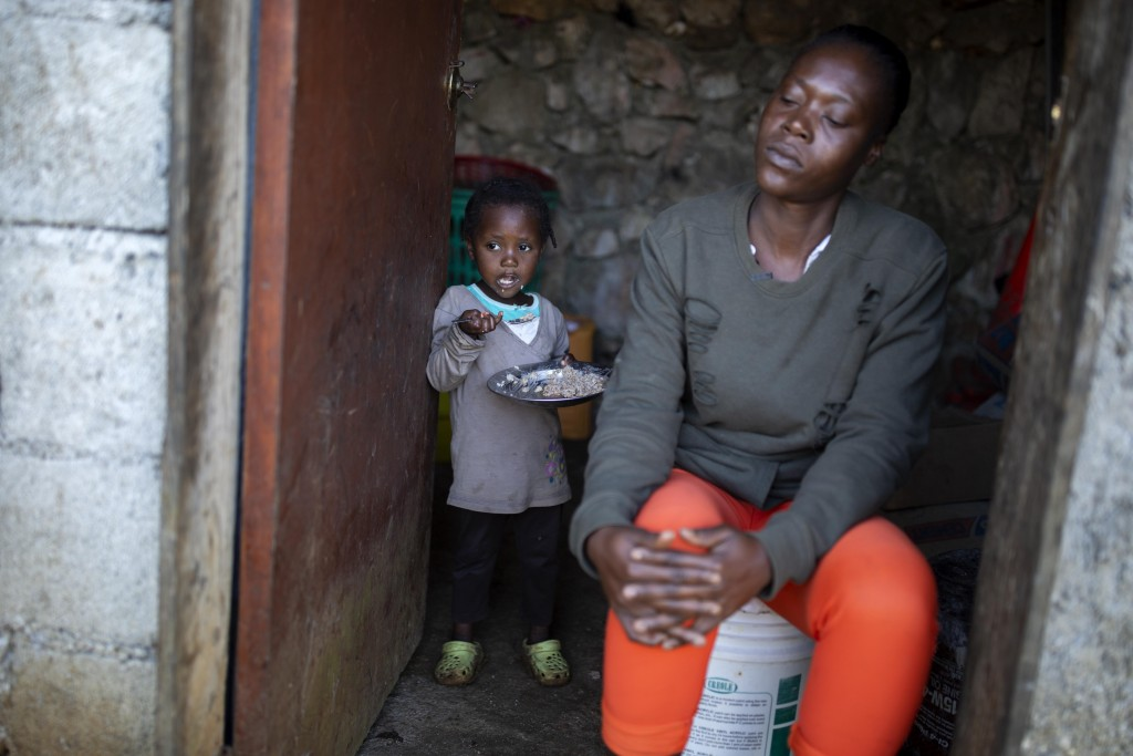 Two-year-old Badinal St. Juste eats rice behind her mother Tania Caristan at their home in Kenscoff, on the outskirts of Port-au-Prince, Haiti, March ...