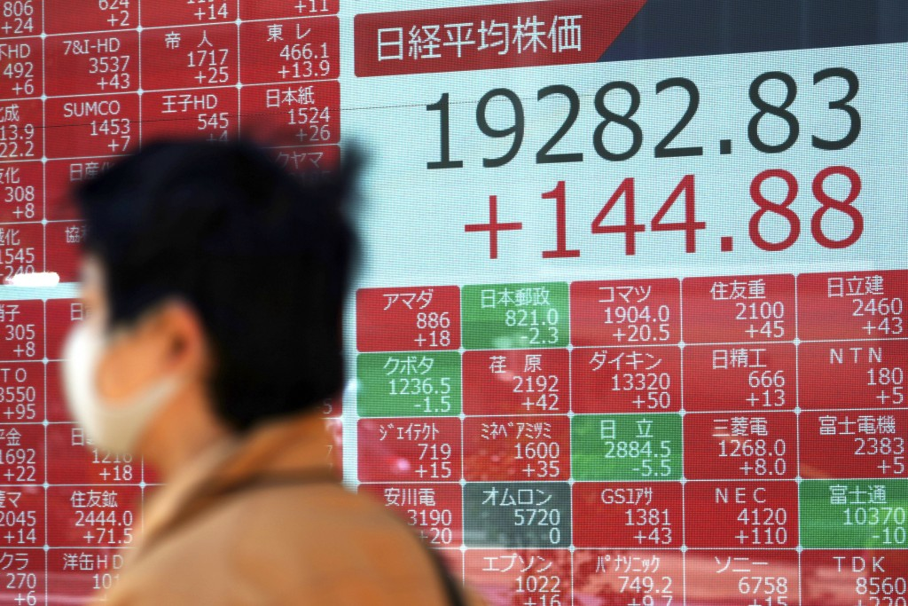 A man wearing a mask against the spread of the new coronavirus walks past an electronic stock board showing Japan's Nikkei 225 index at a securities f...