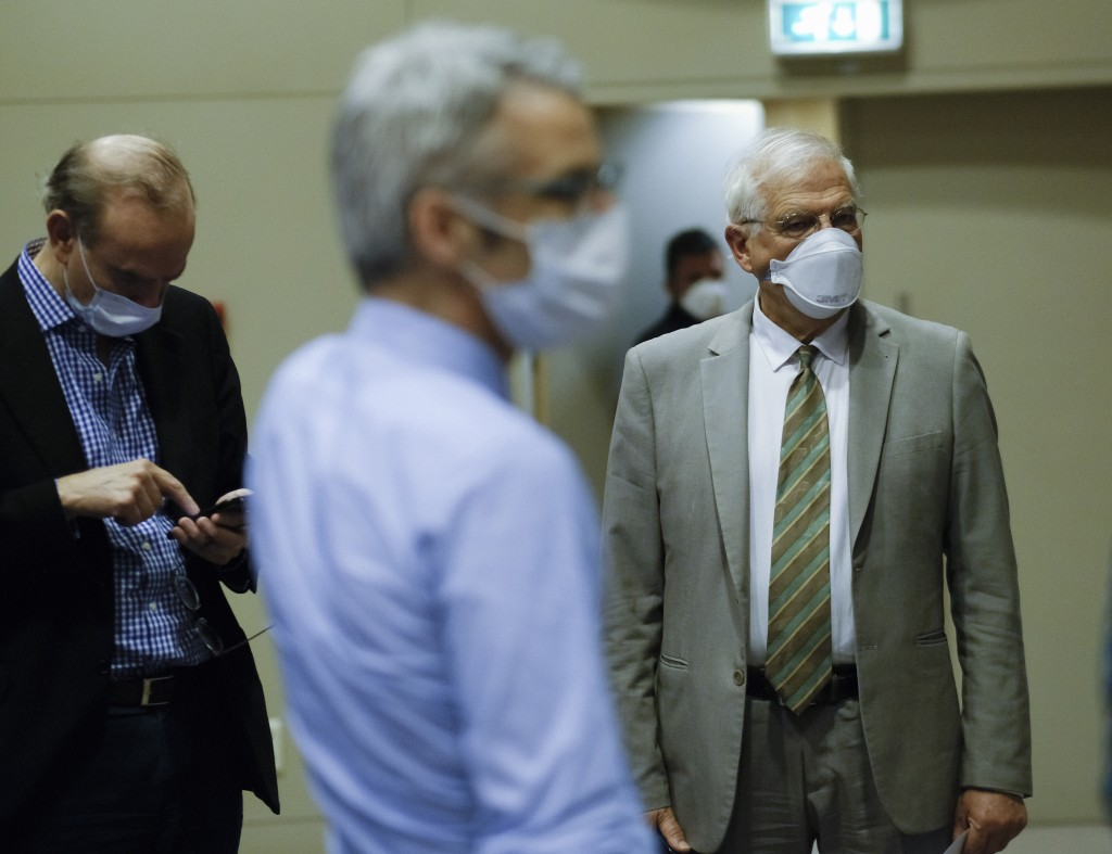 European Union foreign policy chief Josep Borrell, right, wears a mouth mask after addressing a video press conference at the conclusion of a video co...