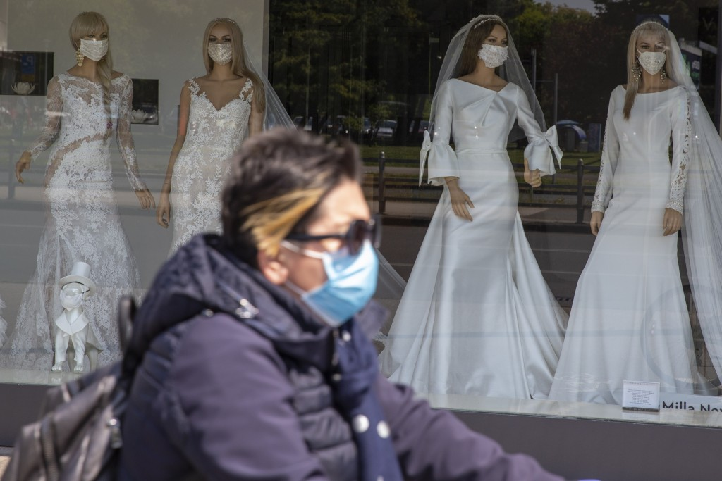 A cyclist wearing a protective mask to protect against coronavirus rides past a wedding dress store with mannequins wearing face masks, in Zagreb, Cro...