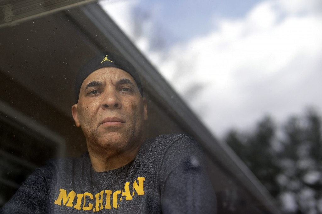 Chuck Christian, of Randolph, Mass., the first former Michigan football player to publicly say that a team doctor abused him, looks through a window i...
