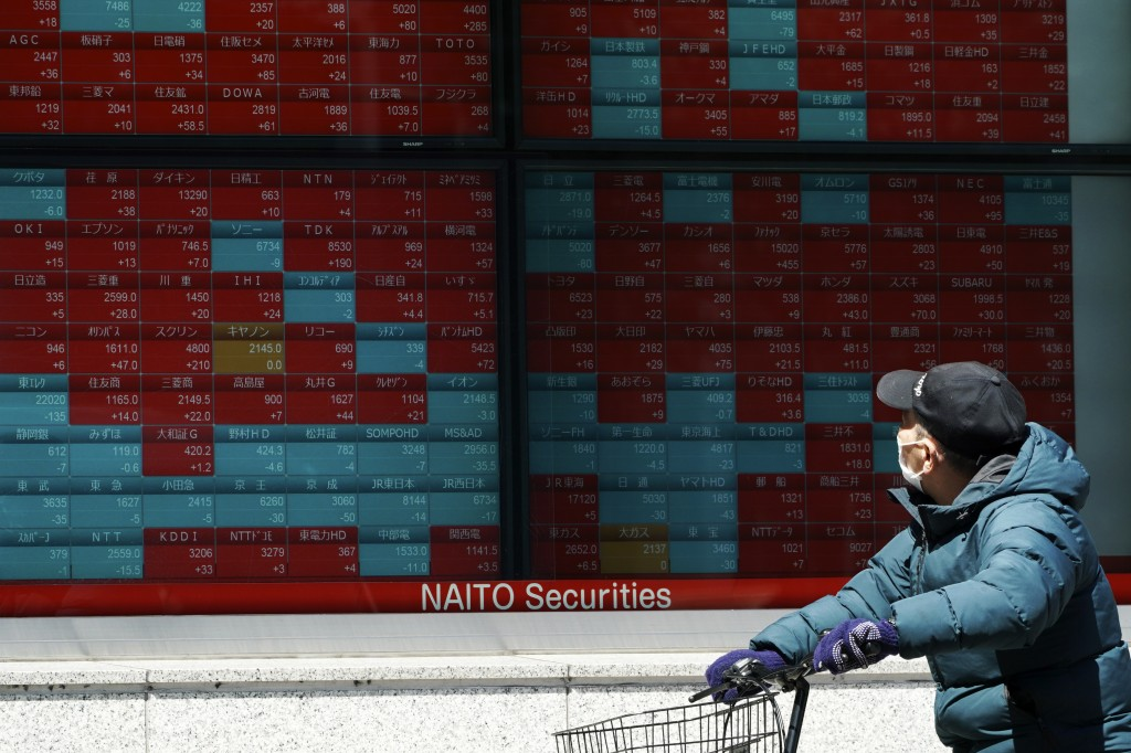 A man wearing a mask against the spread of the new coronavirus looks at an electronic stock board showing Japan's Nikkei 225 index at a securities fir...
